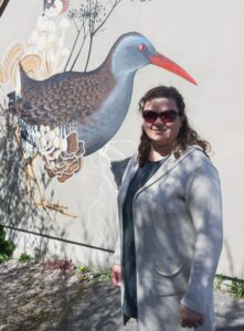 Jessie standing in front of a mural